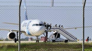 Passengers evacuate the hijacked plane.