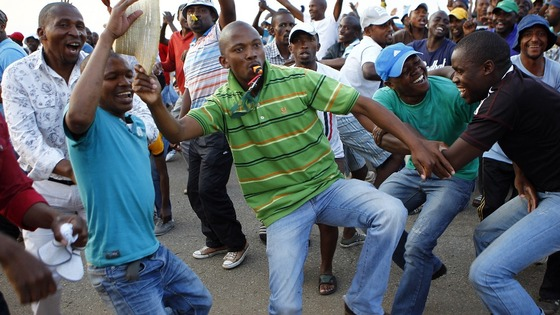 Striking miners dance and cheer after they were informed of a 22 percent wage increase offer outside Lonmin's Marikana mine