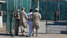 A prisoner is led into Guantanamo Bay by US forces