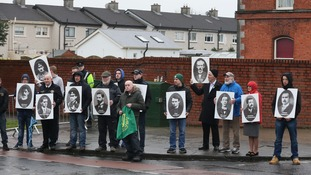 Protesters hold placards outside Glasnevin cemetery in Dublin