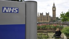 NHS sign with House of Commons in the background