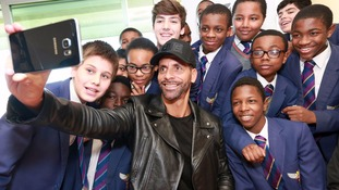 Rio Ferdinand takes a selfie with schoolchildren