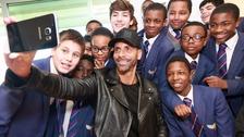 Rio Ferdinand takes a selfie with schoolchildren