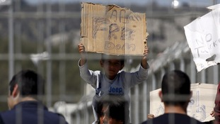 A migrant boy who will be returned to Turkey holds a placard during a demonstration inside the Moria registration centre on the Greek island of Lesbos