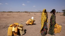 Two women wait to collect water in drought stricken Ethiopia.