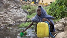 A woman collects water from a stream outside the village of Tsemera i