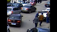Onlookers rush to pull the woman from under the vehicle