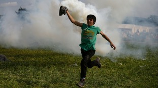 A protesting migrant runs with a teargas canister to throw it over a border fence towards Macedonia