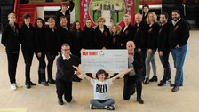 Lee Hall (front left) and Hayden May, who plays Billy (centre) present a cheque to Malcolm Farrow (right) of the East Durham Trust