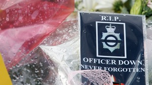 "A card that reads: ""RIP OFFICER DOWN NEVER FORGOTTEN"""