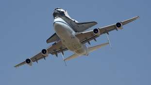 The space shuttle Endeavour, carried piggyback atop a Boeing 747 jumbo jet, lands at Edwards Air Force Base in California