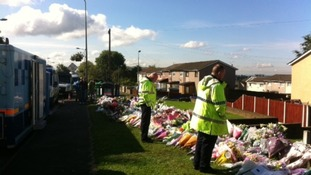 Police officers continue to lay flowers and pay their respects where two of their colleagues were killed.