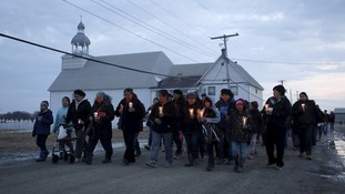 People take part in a march and candlelight vigil in the Attawapiskat First Nation