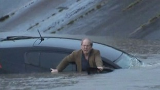 TV reporter helps rescue man from car sinking in floodwater