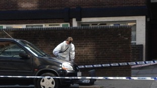Forensics examine the scene in the Canary Wharf district of London where a Russian banker was killed on Tuesday.