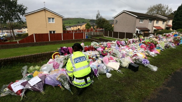 A police officer looks at flowers left at the scene of the shooting of PCs Fiona Bone, 32, and Nicola Hughes, 23, in Greater Manchester.