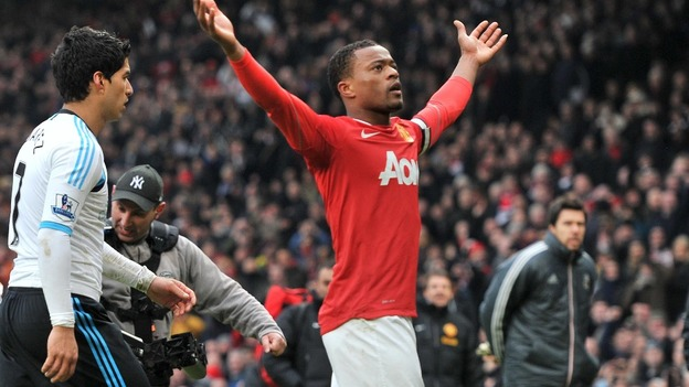 Manchester United&#x27;s Patrice Evra celebrates victory as Liverpool&#x27;s Luis Suarez walks off during last season&#x27;s match between the sides.