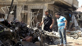 Two men inspect damaged motorcycles after an airstrike on a market in the town of Maarat al-Numan.