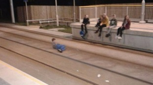 Boy lying on Metrolink track