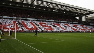 Supporters hold up coloured cards in memory of the Hillsborough disaster at Anfield in Liverpool.