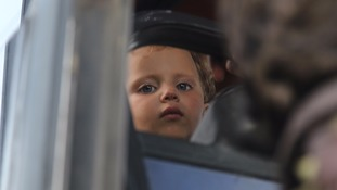 A child waits inside a bus transporting evacuees.