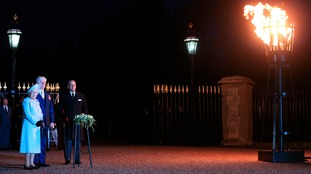 Queen Elizabeth II accompanied by the Duke of Edinburgh (right) lights the first of over 200 beacons to commemorate the 70th anniversary of VE Day at Windsor Castle in May 2015