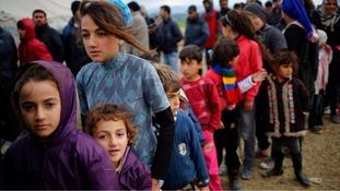 Refugees queue for tea at a makeshift camp.