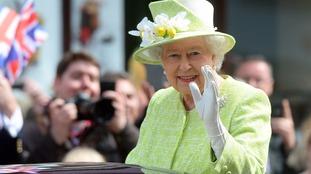 Queen Elizabeth II waves to well wishers from a open top Range Rover