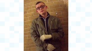 Fairweather in handcuffs and wearing the gardening gloves