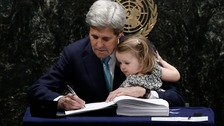 US Secretary of State John Kerry holds his two-year-old granddaughter as he signs the Paris agreement on climate change.