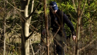 A police officer searches a wooded area at Royston Heath