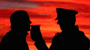 A police officer breathalysing a man silhouetted against an orange sky