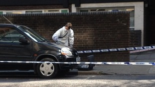Forensic teams examine the crime scene on Byng Street, east London