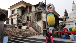A Nepalese woman rests in front of a damaged monastery at the world heritage Swayambhunath Stupa.