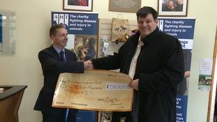 Mark Labbett hands cheque to Animal Health Trust in Newmarket