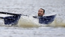 A man is seen in the water during the Oxford vs Cambridge boat race in the River Thames