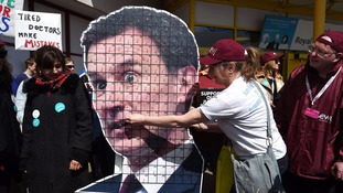 A CWU member pins a pin to a cardboard cut out of Jeremy Hunt.