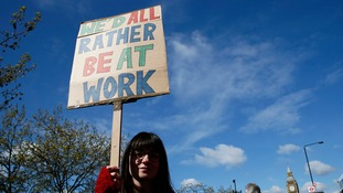 One junior doctor holds a 'we'd rather be work' banner.