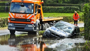 BMW in a ditch surrounded and submerged in flood water on Bristol Road in North Somerset after heavy rain affects roads across South West.