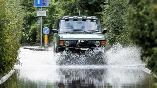 A 4x4 vehicle emerges from flood water that has closed a road on Sleep Lane, Witchurch near Bristol after heavy rain.