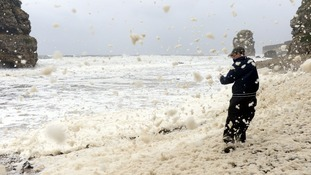 Aron Martin, 17, on Marsden beach near South Shields as heavy seas cause lots of foam along the beach.