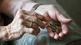 An elderly woman counting loose change.