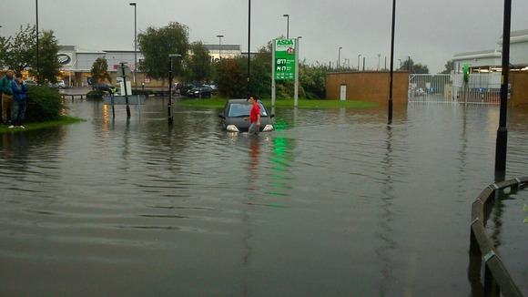 A driver wades through water at a retail park in Wigan