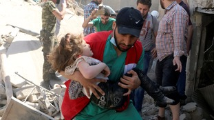 A child carried from the rubble in rebel-held Aleppo following an airstrike