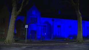 A number of buildings are lit up in blue