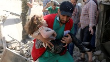 A child is carried to safety at the site of the airstrike in Aleppo.