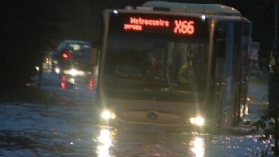 A bus is submerged in rain water in Gateshead today.