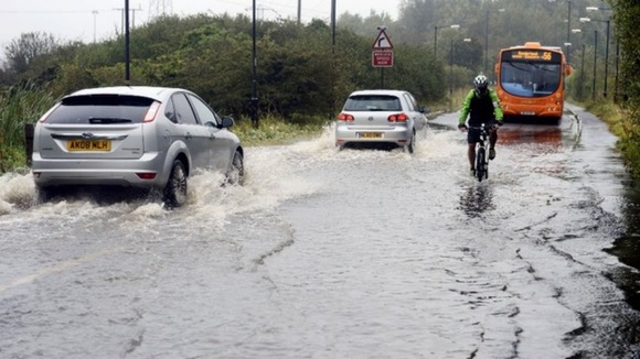Motorists make their way through flood water in Washington, Tyne and Wear.