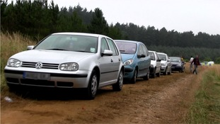 Cars parked near field for illegal rave.