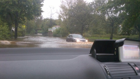 Cars struggle through flooding in St Helens